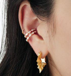 Gros plan sur une oreille avec une composition de boucles d'oreilles Maria Tash, des studs, des anneaux, des pendents agencés tout autour de l'oreille