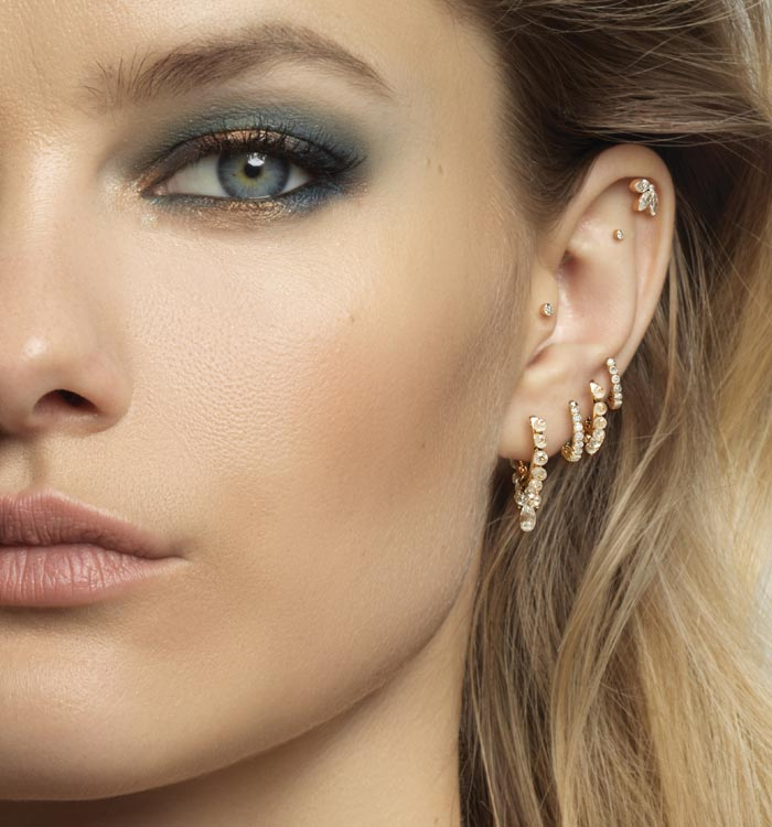 Model wearing studs and rings of all sizes on every part of the ear, whether the helix at the top, the tragus just below or even the conch further inside.