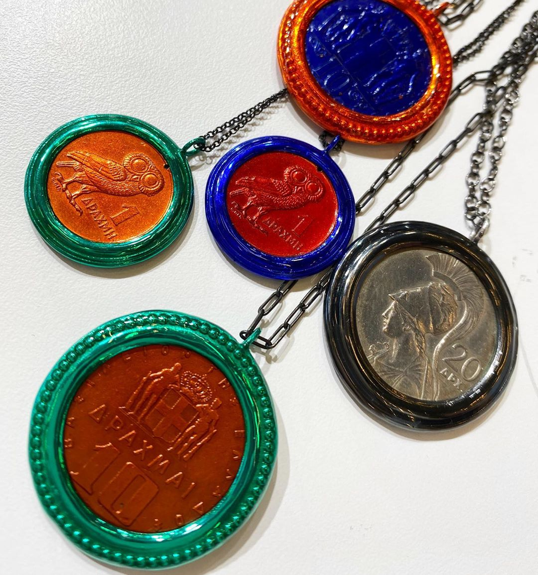 """[JEWELRY, A PASSPORT TO GREECE] I particularity like the money-money collection of @mariakaprilifinejewelry Kaprili colors #ancientcoins and their settings in orange, electric blue, green and yellow, using an electrostatic technique """"I got the idea when I inherited my uncle's coin collection,"""" she says. Coins were vital objects in Greek culture: they were given as gifts at special occasions in life, like marriage, when the family would provide the #coins decorating the bride's pectoral jewelry as a dowry. They were also treasure that could be easily carried away in times of hardship. More in my bio  #ilovegreece #discovergreece #kolonaki #athens #greekjewelry @reasonstovisitgreece @discover.greece @visitgreecegr @centreculturelhellenique @aegeanairlines"""